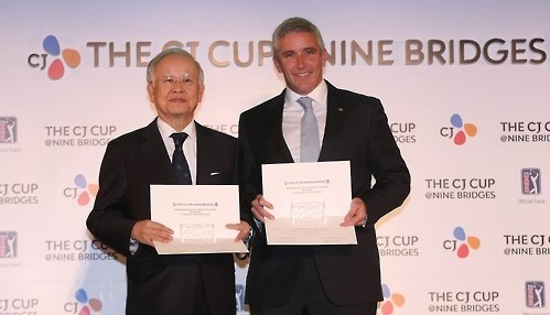 Sohn Kyung-shik, chairman of CJ Group (left), and Jay Monahan, then deputy commissioner of the PGA Tour, pose with their agreements in Seoul after CJ signed on to host the CJ Cup@Nine Bridges, the first PGA Tour event in South Korea. (Yonhap)