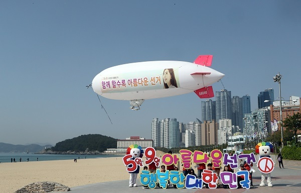 Officials of the National Election Commission fly an airship with a banner campaigning for votes in the May 9 presidential election at Haeundae Beach, in Busan, Thursday. (Yonhap)