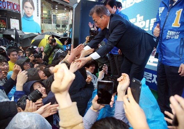 Moon Jae-in (R), the candidate of the liberal Democratic Party in the upcoming presidential election, shakes hands with a supporter while staging a street campaign in Daegu, 300 kilometers south of Seoul, on April 17, 2017. (Yonhap)
