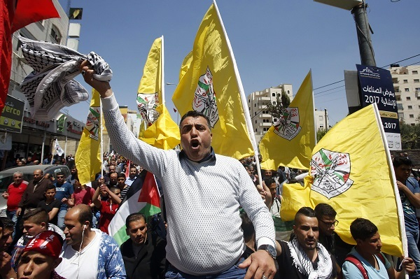 A man holds a keffiyeh before flags of the Fatah movement during a rally in the West Bank town of Hebron to show support to Palestinians detained in Israeli jails after hundreds of them launched a hunger strike on April 17, 2017. (AFP-Yonhap)