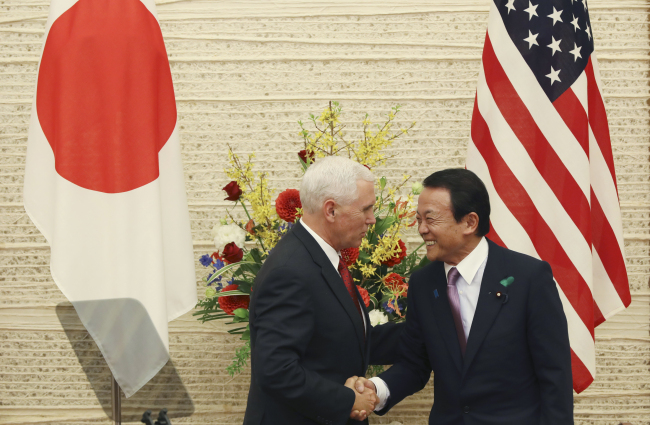 US Vice President Mike Pence (left) and Japanese Deputy Prime Minister and Finance Minister Taro Aso shake hands as they end the joint press conference at the prime minister's office in Tokyo, Tuesday. (AP)