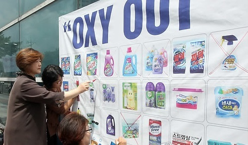 members of civic consumers' groups cross out the images of the products of Oxy Reckitt Benckiser at a news conference calling for the suspension of products' marketing in front of a supermarket in Daejeon, 164 kilometers south of Seoul. (Yonhap)
