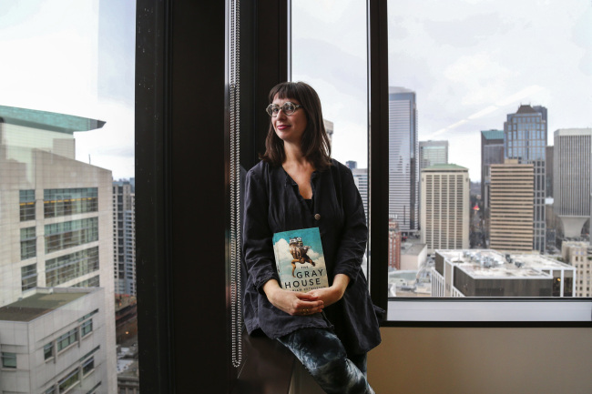 "Gabriella Page-Fort, the editorial director for AmazonCrossing, poses for a portrait on March 8, in Seattle, while holding a copy of the book ""The Gray House,"" by Mariam Petrosyan. (Seattle Times/TNS)"