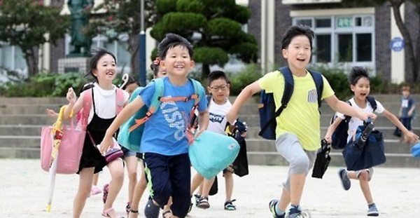 Students from an elementary school in Daejeon, about 160 kilometers south of Seoul, run from the school grounds as summer vacation starts. (Yonhap)