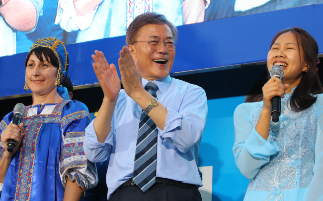 Moon Jae-in (center) of Democratic Party of Korea claps next to a Vietnamese immigrant (right) in an election campaign in Uijeongbu, Gyeonggi Province on Monday. (Yonhap)