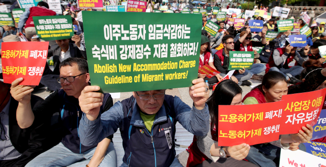 People hold signs calling for better conditions for migrant workers during a May Day demonstration Sunday. (Yonhap)