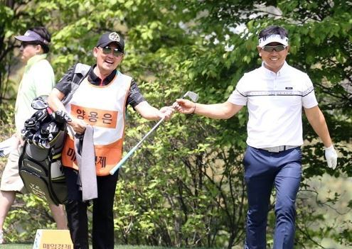 Yang Yong-eun (right) hands a club to his celebrity caddie, singer Lee Seung-chul, at the second hole during the first round of the GS Caltex Maekyung Open on the KPGA Tour at Nam Seoul Country Club in Seongnam, Gyeonggi Province. (KPGA Tour)