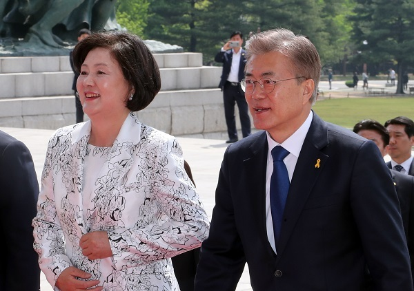 South Korea's new first lady Kim Jung-sook (left) holds newly elected president Moon Jae-in's hand. (Yonhap)