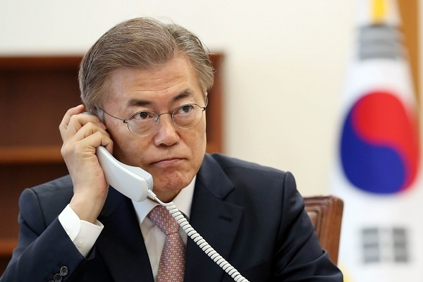 President Moon Jae-in sits in his Cheong Wa Dae office on Thursday, talking by phone with Chinese counterpart Xi Jinping. (Yonhap)