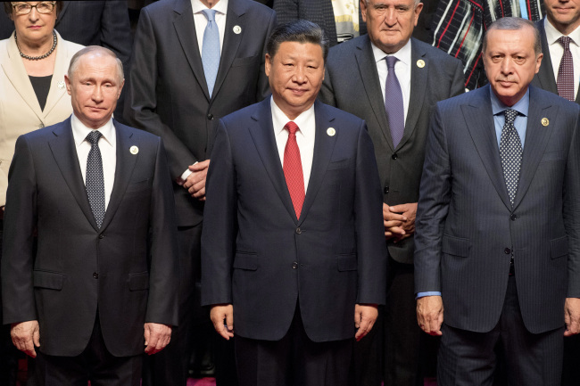 Chinese President Xi Jinping (center) stands with Russian President Vladimir Putin (left), Turkish President Recep Tayyip Erdogan (right) and other leaders to pose for a group photo prior to the opening ceremony of the Belt and Road Forum at the China National Convention Center in Beijing Sunday. AP-Yonhap