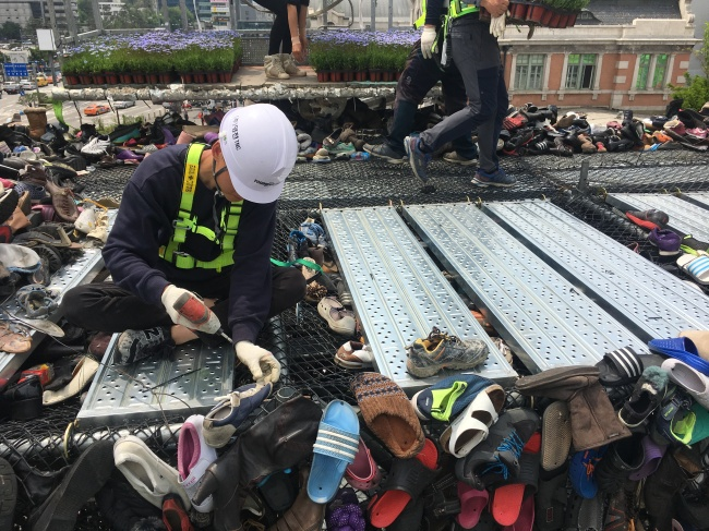 Workers hang worn-out shoes on Shoes Tree on Seoullo 7017, Seoul's soon-to-open pedestrian-friendly park, near Seoul Station on Tuesday. (Kim Da-sol/The Korea Herald)