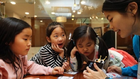 In this photo taken on Dec. 14, 2016, a member of the nonprofit foundation Like Lion teaches kids basic coding at a kids cafe in Seoul. (Yonhap)