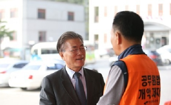 This photo, taken on Oct. 19, 2016, shows Moon Jae-in, former leader of the liberal Democratic Party of Korea, shaking hands with a unionized work of Jecheon city, about 170 kilometers southeast of Seoul. (Yonhap)
