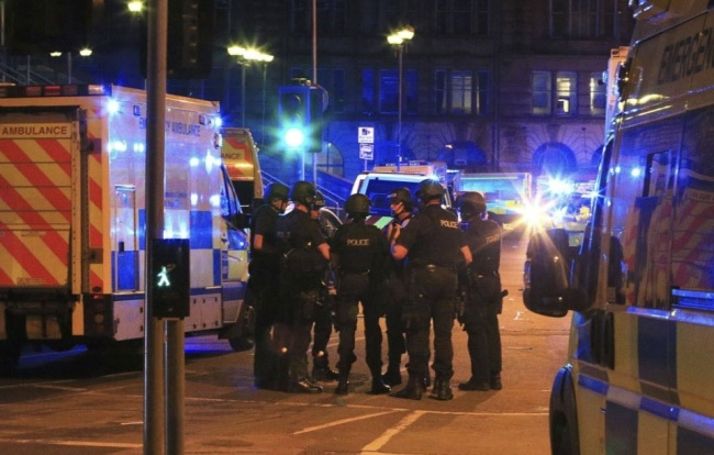Armed police gather at Manchester Arena after reports of an explosion at the venue during an Ariana Grande gig in Mancehester, England Monday. (AP-Yonhap)
