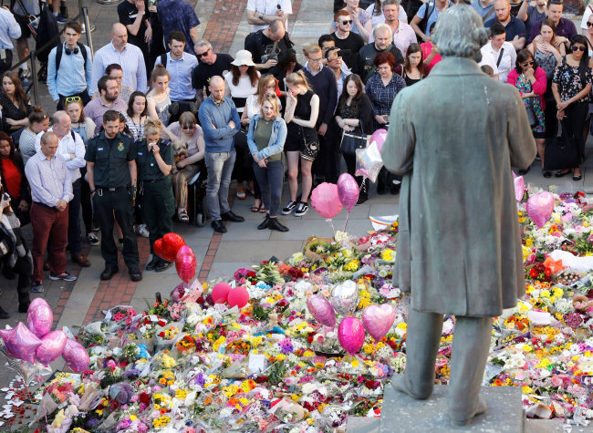 People look at floral tributes for the victims of the Manchester Arena attack, in St. Ann's Square, in central Manchester, England, Thursday. (Reuters-Yonhap)