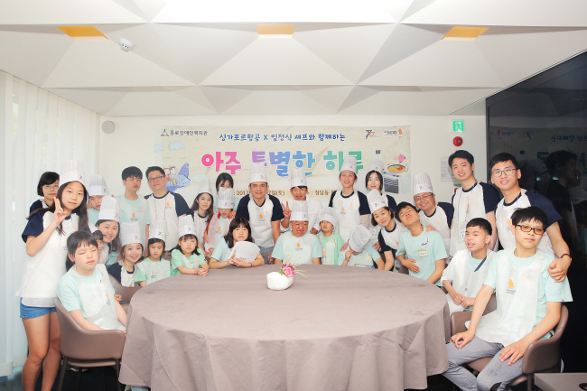 A VERY SPECIAL DAY -- Participants pose for a photo during an event on Saturday organized by Singapore Airlines and also joined by Singapore Airlines General Manager for the Korean branch Seah Chee Chian (standing, center), offering an opportunity for children with visual impairment and their families to cook in-flight meals with Chef Yim Jung-sik of Michelin-starred restaurant Jungsik. The event is part of the airline's corporate social responsibility program and has been held since 2012. (Singapore Airlines)