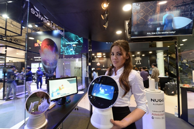 A Spanish model poses with SK Telecom's artificial intelligence robot Albert at the Mobile World Congress held in Barcelona, Spain, in February. (SK Telecom)