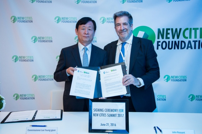Commissioner of Incheon Free Economic Zone Authority Lee Young-geun (left) and NewCities Foundation Chairman John Rossant pose at a signing ceremony for the NewCities Summit 2017 on June 21, 2016, after Songdo was selected as the site to host the NewCities Summit 2017. (NewCities Foundation)