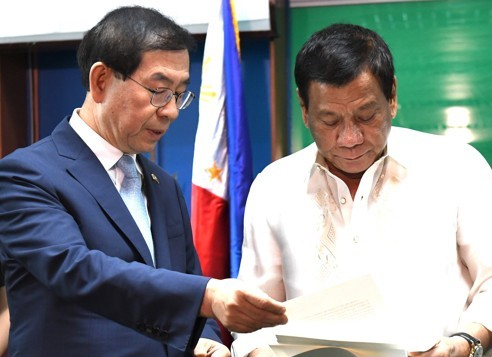 Philippine President Rodrigo Duterte (R) reads a personal letter from South Korean President Moon Jae-in that was presented by Seoul Mayor Park Won-soon, Moon's special envoy to the Association of Southeast Asian Nations (ASEAN), in the southern Philippine city of Davao on May 22, 2017, in this provided photo. (Yonhap)