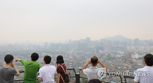 This May 2017 file photo shows people looking at the landscape of downtown Seoul on the slope of the city`s Mount Nam as the city is covered in a thick haze caused by fine dust. (Yonhap)