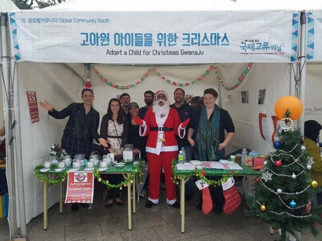 Sarah Elizabeth Hale (right) stands with other volunteers at the Adopt-a-Child for Christmas booth during Gwangju International Community Day in October.