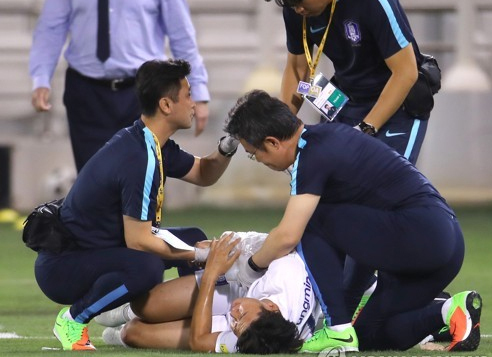 South Korean player Son Heung-min (center) is being treated for an arm injury after an awkward fall during a World Cup qualification match against Qatar at Jassim Bin Hamad Stadium in Doha on June 13, 2017. (Yonhap)