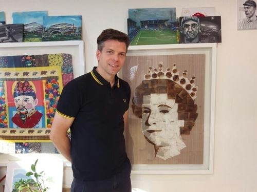 Seoul-based British artist Andy Brown poses next to his portrait of Queen Elizabeth II that`s made of tea bags in his Seoul apartment on June 16, 2017. (Yonhap)