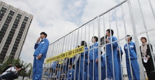 Protesters are trapped inside what looks like a prison in Seoul on May 15, 2017, as they rally to demand the government not punish conscientious objectors and introduce alternative service options for them in observance of the International Conscientious Objectors Day that fell on the same day. (Yonhap)