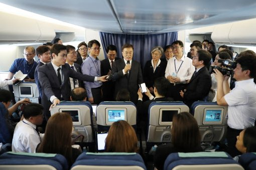 President Moon Jae-in (holding a mic) speaks to reporters while aboard Air Force One en route to Washington on June 28, 2017, for his summit with US President Donald Trump later in the week. (Yonhap)