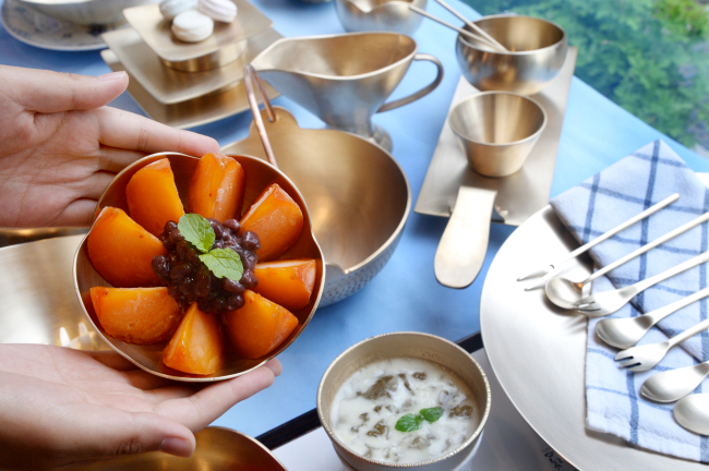 A plate of ripe persimmon and red bean paste (left) and iced yuja tea at Cafe Noshi (Park Hyun-koo/The Korea Herald)