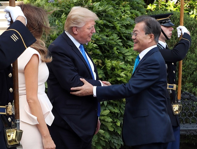 South Korean President Moon Jae-in (right) shakes hands with US President Donald Trump as he and his wife, Kim Jung-sook, arrived at the White House on June 29, 2017, for a dinner hosted by Trump and his wife, Melania, on the eve of the first Korea-US summit under the countries` new administrations. (Yonhap)
