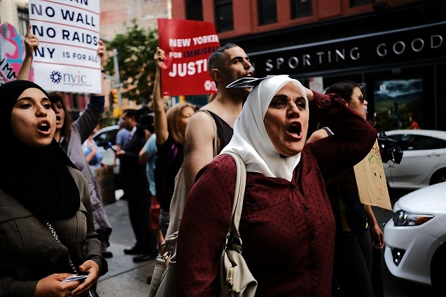 Immingrants join activists for an evening protest in Manhattan hours before a revised version of President Donald Trump`s travel ban that was approved by the Supreme Court is to take effect on June 29, 2017 in New York City. (AFP-Yonhap)