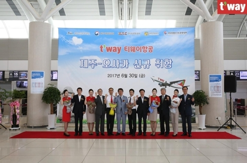 The company`s CEO Jeong Hong-geun (sixth from left) and employees celebrate the opening of the Jeju Island-Osaka route at Jeju International Airport on June 30, 2017. (T`way Air)
