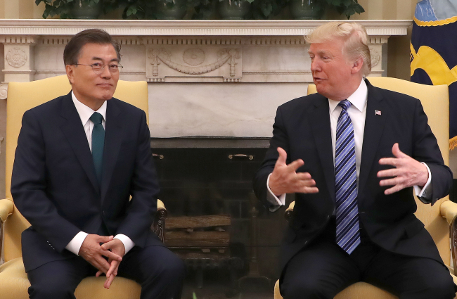 US President Donald Trump (right) speaks at a summit with President Moon Jae-in during their summit at the White House in Washington on Friday. (Yonhap)