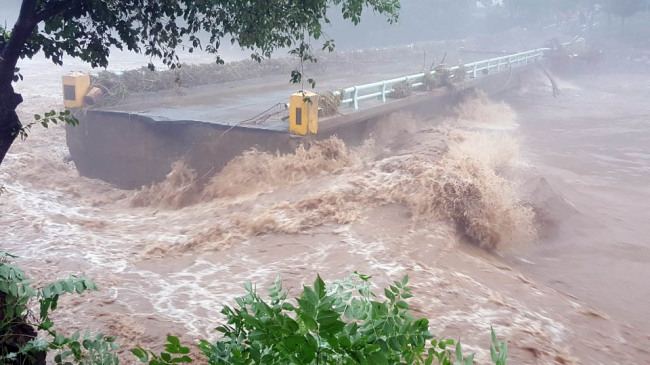 A bridge is destroyed in Hongcheon Country in Gangwon Province where 343 millimeters of rain fell overnight. (Yonhap)
