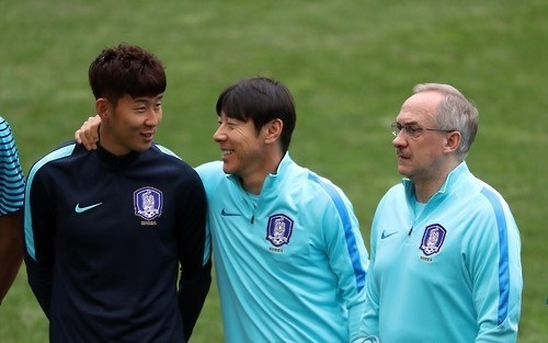 In this file photo taken on Aug. 29, 2016, Shin Tae-yong (2nd from L), then assistant coach to South Korea football head coach Uli Stielike (R), talks with Son Heung-min before training at Seoul World Cup Stadium in Seoul. (Yonhap)