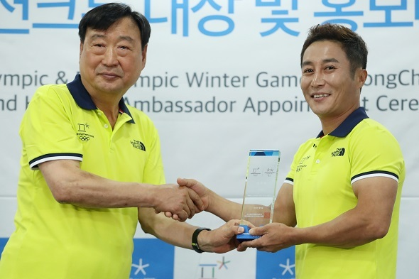 Lee Hee-beom (L), chief of the PyeongChang Organizing Committee for the 2018 Olympic & Paralympic Winter Games, shakes hands with South Korean comedian Kim Byoung-man after the latter was appointed honorary ambassador for the PyeongChang Games on July 5, 2017. (Yonhap)