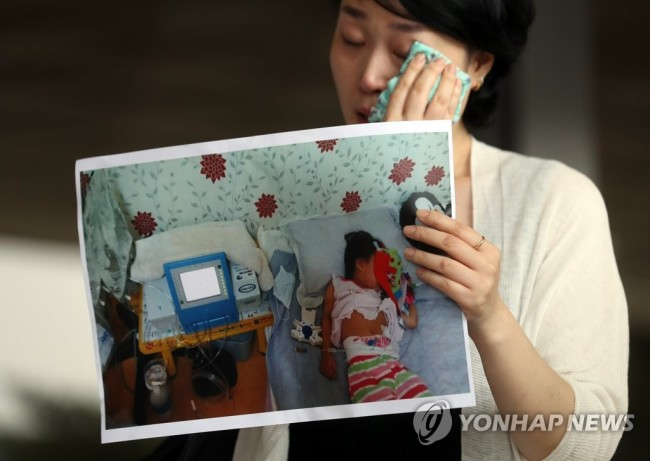 Plaintiff Choi Eun-ju holds a picture of her daughter in front of Seoul District Prosecutors Office on Wednesday. (Yonhap)