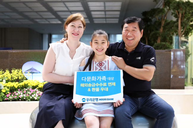 A family pose at the main branch of Woori Bank in Seoul Sunday, promoting the special service designed for multicultural families. (Woori Bank)