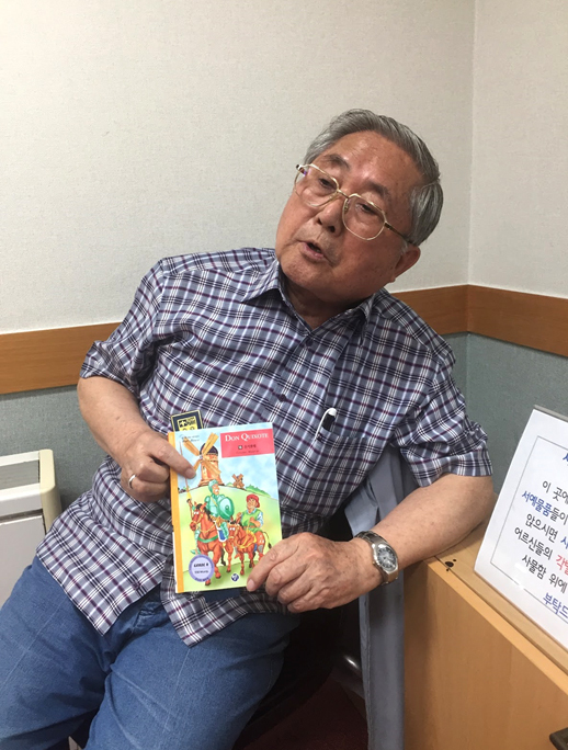 """Lee Jim-kee holds his favorite book to teach with, """"Don Quixote."""" (Aparna Balakumar)"""