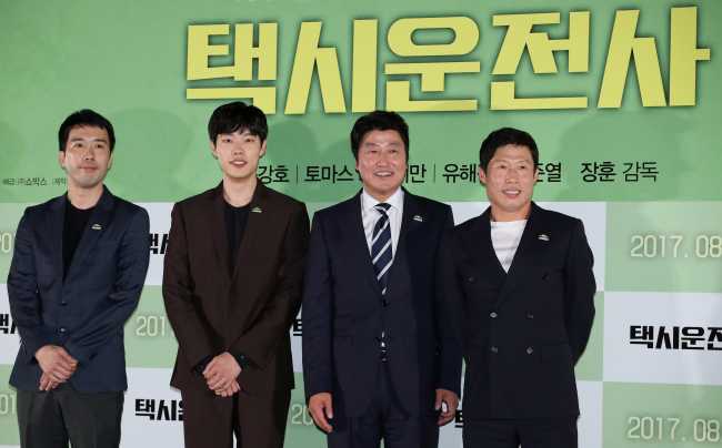 "From left: Director Jang Hoon and actors Ryu Jun-yeol, Song Kang-ho and Yoo Hae-jin speak to reporters after the press screening of ""A Taxi Driver"" at the Megabox Coex theater in Samseong-dong, Seoul, Monday. (Yonhap)"