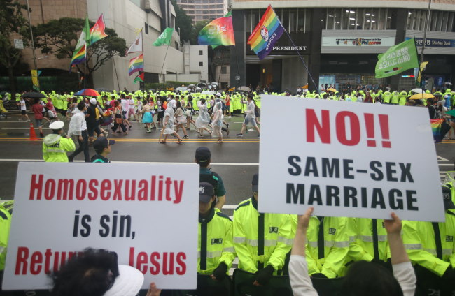"Anti-gay protestors hold up placards reading ""homosexuality is sin, return to Jesus"" and ""No!! Same-sex marriage"" on the sidewalk as pro-gay participants parade through central Seoul during the pride parade on Saturday. (Yonhap)"