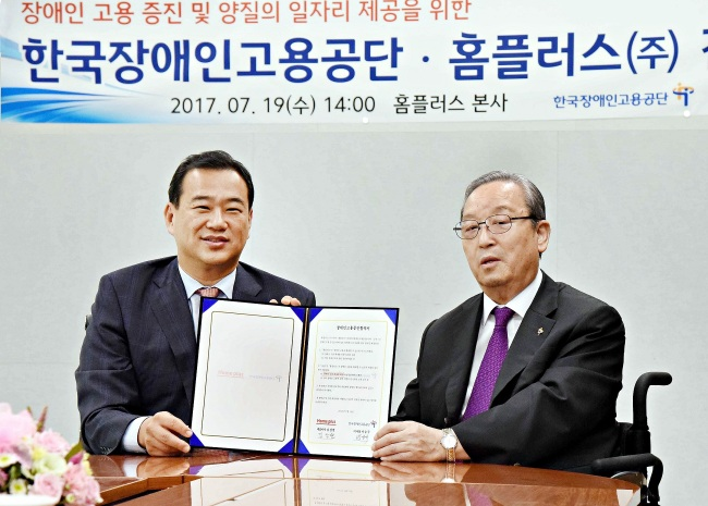 Homeplus CEO Kim Sang-hyun (left) and KEAD President Park Seung-Kyu hold up a joint agreement signed Wednesday at the Homeplus headquarters in Seoul. (Homeplus)