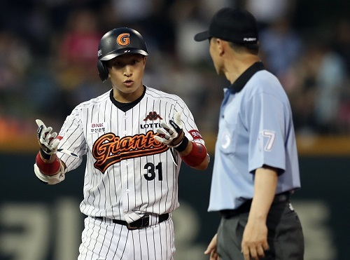 Lotte Giants right fielder Son Ah-seop confers with an umpire during video review of his hit in yesterday's game. (Yonhap)