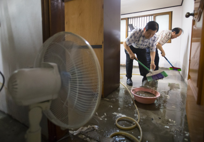 Residents clean up the house in Incheon, Monday. (Yonhap)