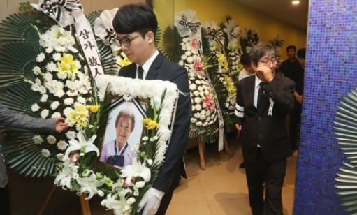 A participant carries a portrait of Kim Kun-ja, a victim of Japan`s wartime sexual enslavement, during her funeral at a hospital south of Seoul on July 25, 2017. Kim, who died two days ago at the age of 91, was one of tens of thousands of young Korean girls, known as