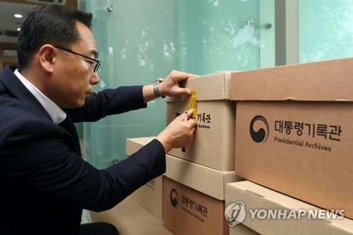 An official at the presidential office put tape on the box containing presidential documents found in the offices of presidnetial secretaries, to deliver them to the Presidential Archive at the Blue House on July 14. (Yonhap)