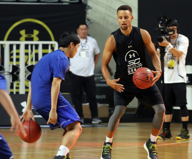 Stephen Curry teaches ball-handling to a youth basketball clinic participant at Jangchung Gymnasium in Seoul on Thursday. (Yonhap)
