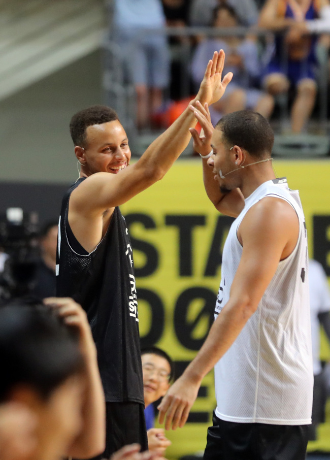 Stephen Curry high-fives his brother Seth, a point guard for the Dallas Mavericks, during a youth basketball clinic at Jangchung Gymnasium in Seoul on Thursday. (Yonhap)