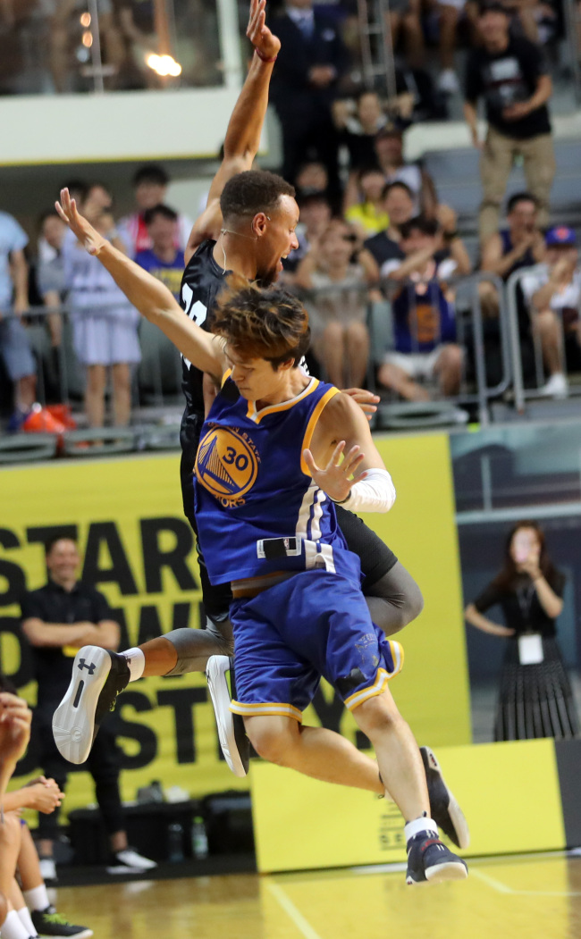 Stephen Curry body-bumps a fan during a youth basketball clinic at Jangchung Gymnasium in Seoul on Thursday. (Yonhap)
